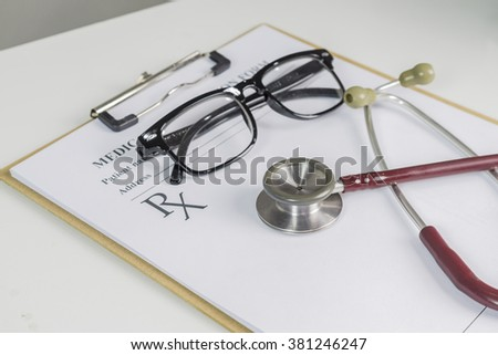 stethoscope and rescription form lying on table with  and pen,glasses,pencil. Medicine or pharmacy concept. Empty medical form ready to be used. Medicine doctor tools and instruments at working table