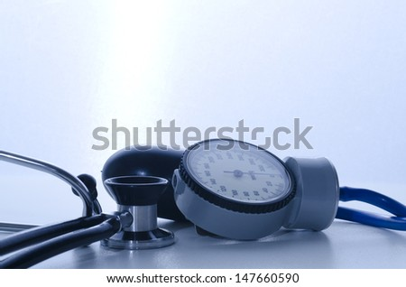 stethoscope and sphygmomanometer medical instruments with blue lights - stock photo