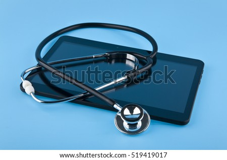 stethoscope and tablet on blue background closeup