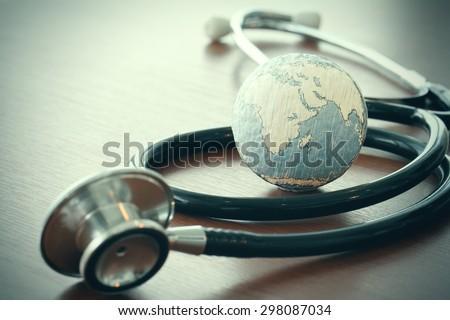 stethoscope and texture globe with digital tablet as medical network concept - stock photo