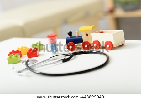 Stethoscope and toy on desk - stock photo