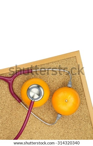Stethoscope examining orange on a cork board. Medical equipment, Healthy food eating concept.