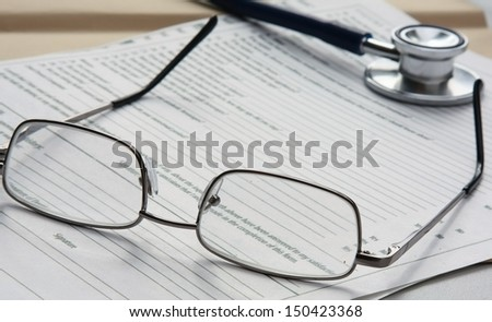 stethoscope , folder with papers and glasses - stock photo
