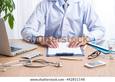 Stethoscope head lying on medical forms on clipboards while medicine doctor working in background. Health care, insurance and help concept. Physician ready to examine patient - stock photo
