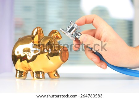 Stethoscope in hand and piggybank on white table..