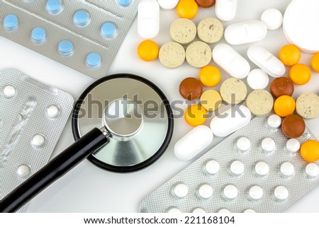 Stethoscope in the middle of pile of colorful pills and blister packs - stock photo