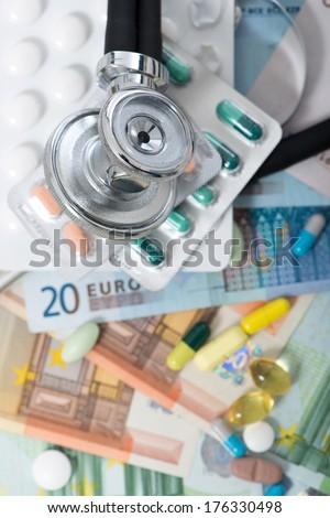 Stethoscope lying on many banknotes - stock photo