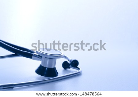 stethoscope medical instrument with blue lights falling on it - stock photo