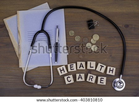 Stethoscope, money, pen with notebook and text: Health care - stock photo