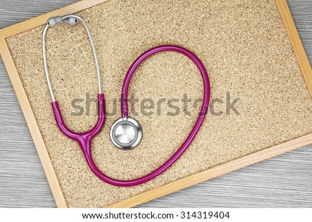 Stethoscope on a cork board, Medical equipment. Examining equipment. (Vintage Style Color) - stock photo