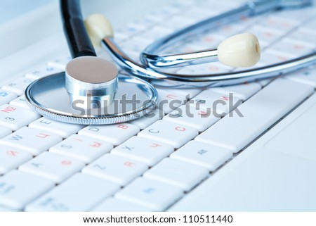 Stethoscope on a modern pc keyboard - stock photo