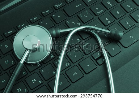 Stethoscope on black laptop keyboard - stock photo
