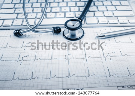 Stethoscope on cardiogram concept for heart care on the desk.blue toned images. - stock photo