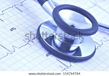 Stethoscope on ecg graph with blue tint - stock photo