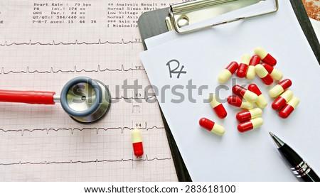 Stethoscope on EKG graphs, drug distribution on the prescription Medical concept - stock photo