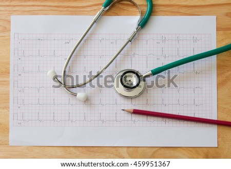 Stethoscope on electrocardiogram and red pencil on table
