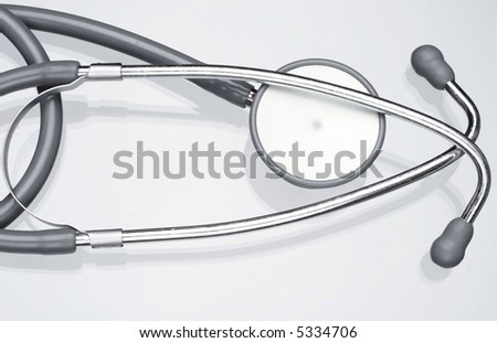 Stethoscope on glass table and white background.