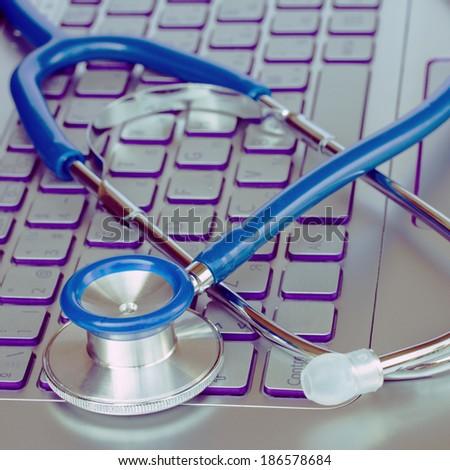 stethoscope on laptop keyboard - modern medicine concept - stock photo