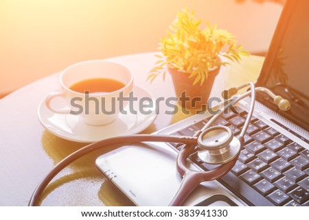 Stethoscope on laptop keyboard,stethoscope on the keyboard of pc,Medical Stethoscope Resting on Desk,relax time doctor,selective focus,vintage color.morning light - stock photo