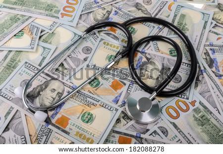 Stethoscope on money background - medical concept - stock photo
