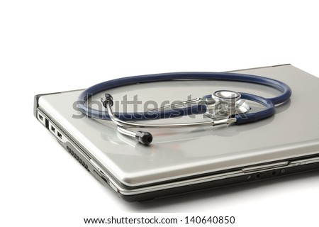 Stethoscope on silver laptop computer - stock photo