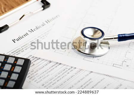 stethoscope on the cardiogram and calculator