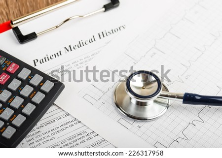stethoscope on the cardiogram and calculator - stock photo