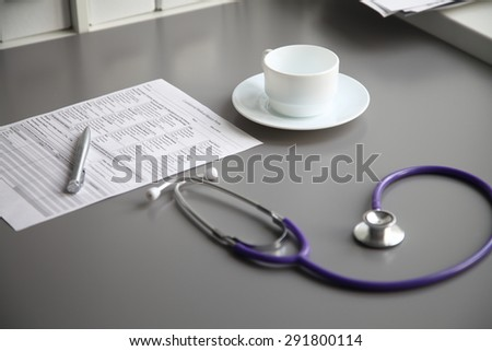 Stethoscope on the grey desk, close up