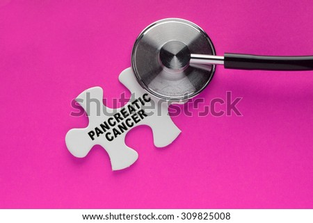 Stethoscope on top of a white jigsaw puzzle with a written word pancreatic cancer on a pink background. Cancer awareness campaign concept.  - stock photo