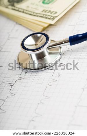 stethoscope over ecg graph and 100 dollar bills  - stock photo