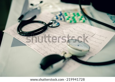 Stethoscope, pills and ECG chart on desk - stock photo