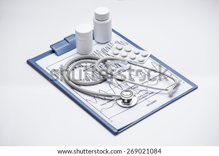 Stethoscope, pills, bottles on blue medical clipboard. Medicine concept. View from the top - stock photo