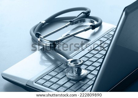 Stethoscope resting on a computer keyboard. - stock photo