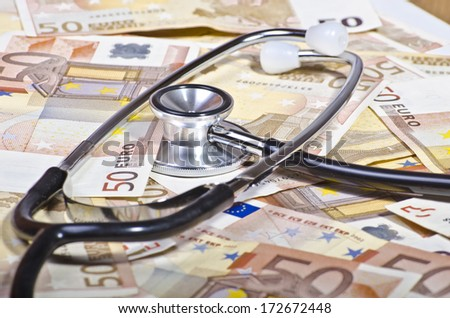 stethoscope surrounded by banknotes and coins suggesting the cost of medical investigation - stock photo