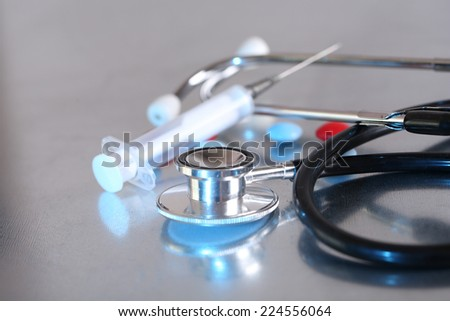 Stethoscope, syringe, pills on light background. Medicine concept - stock photo