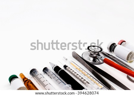 Stethoscope, syringes, scissors, forceps and ampoules on a white medical work surface.
