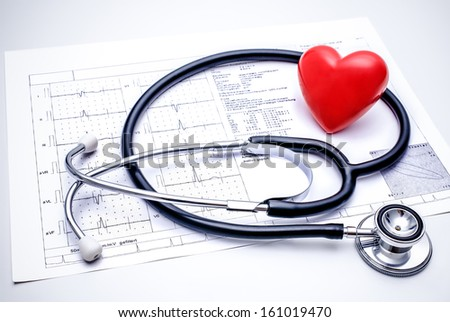 Stethoscope with a red heart on the top of the ECG chart - stock photo