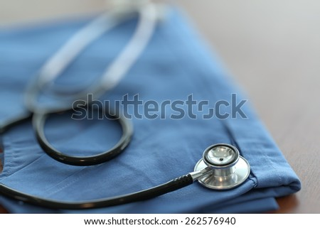 Stethoscope with blue doctor coat on wooden table with shallow DOF evenly matched and background - stock photo