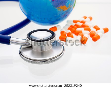 Stethoscope with globe and pills background. Concept for health care or medical.