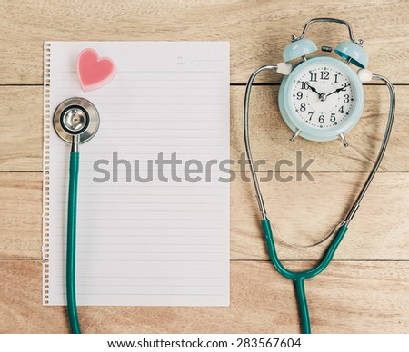 Stethoscope with heart and alarm clock on the table. - stock photo