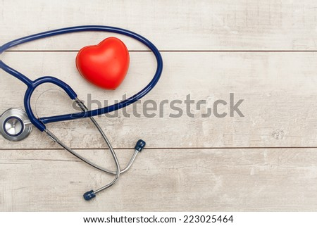 Stethoscope with red heart on a wood background - stock photo