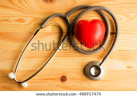 Stethoscope with red heart on a wood background
