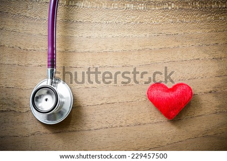 Stethoscope with red heart on wooden background  - stock photo