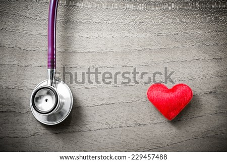 Stethoscope with red heart on wooden background, Medical Concept - stock photo