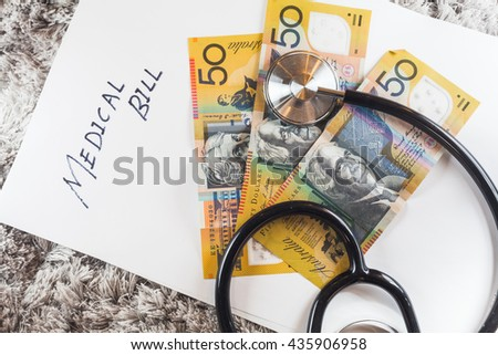 "Stethoscope with wording of ""Medical Bill"" showing expensive healthcare or expensive medical bill with Australia Aussie Bank Notes"