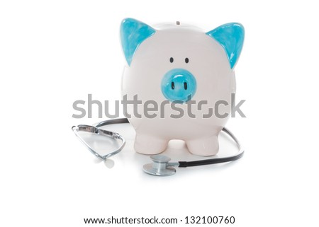 Stethoscope wrapped around blue and white hand painted piggy bank - stock photo