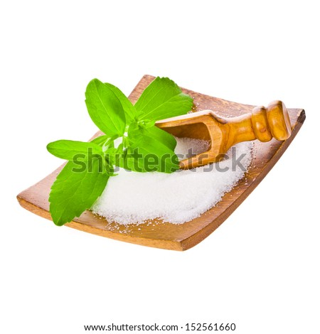 Stevia - plant stevia rebaudiana, green leaves and crystals on a wooden plate with a wooden scoop isolated on white background