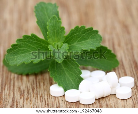 Stevia with tablets on wooden surface - stock photo