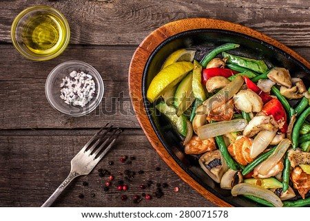Stew chicken with vegetables and mushrooms on a wooden table with fork, pepper, salt, olive oil - stock photo