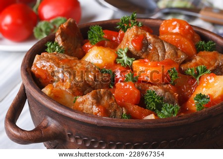 stew in tomato sauce with vegetables close up in a pot. horizontal  - stock photo
